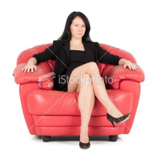 Confident business woman sitting in red chair Royalty Free Stock Photo